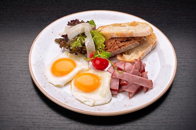 Uova fritte fritte con pomodori, prosciutto e pane tostato ciabatta, su una superficie scura. colazione Foto Premium