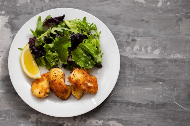 Calamari fritti con insalata e limone sulla zolla bianca Foto Premium
