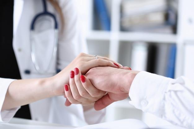 Mano paziente maschio amichevole della stretta femminile del medico Foto Premium