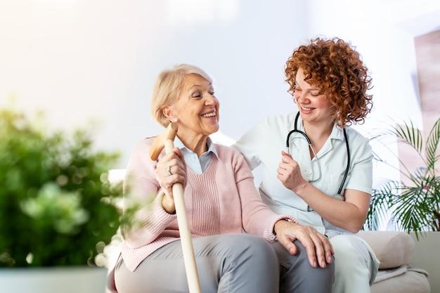 Relazione amichevole tra caregiver sorridente in uniforme e felice donna anziana. giovane infermiera di sostegno che esamina donna senior. Foto Premium