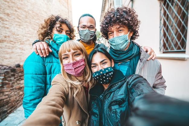 Amici coperti da maschere che si scattano un selfie fuori in città Foto Premium