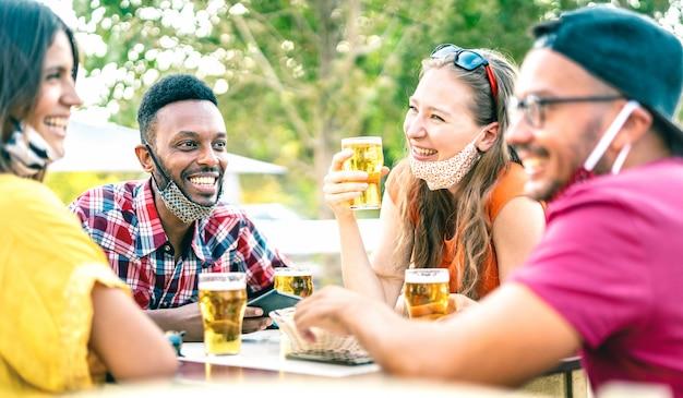 Amici che bevono birra con le maschere aperte - fuoco selettivo sul ragazzo sinistro Foto Premium