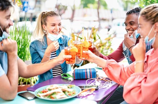 Amici che bevono spritz al cocktail bar con maschere Foto Premium