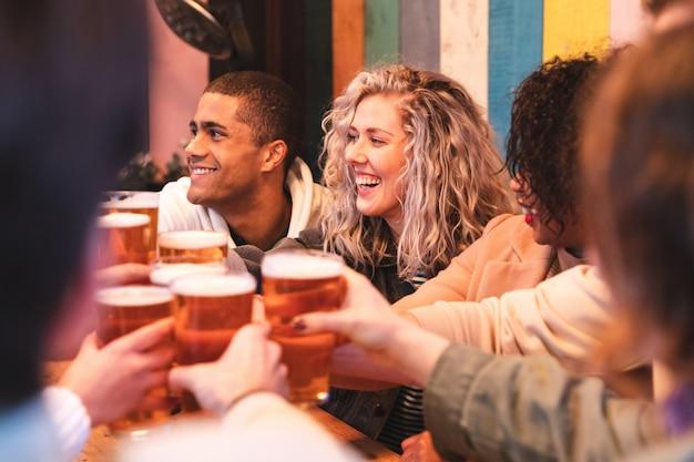 Amici che bevono e che tostano con la birra al pub Foto Premium