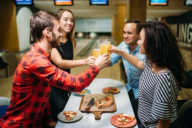Gli amici beve e mangia la pizza nel club di bowling Foto Premium
