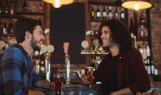 Amici che bevono birra al bancone del bar Foto Premium