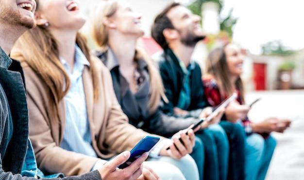 Amici che ridono durante l'utilizzo di smartphone durante la pausa del college universitario Foto Premium
