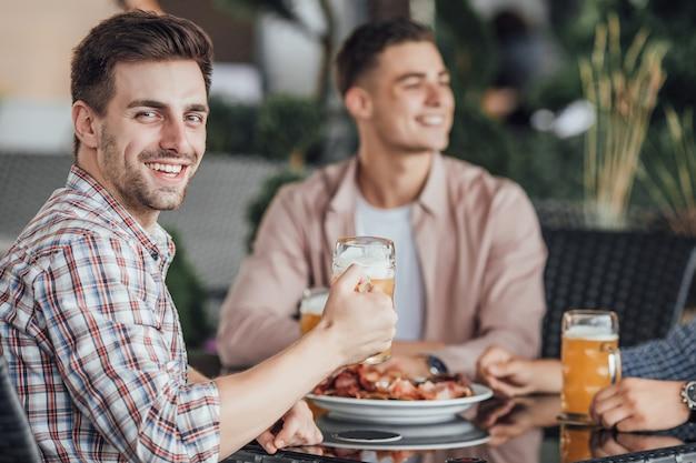 Gli amici trascorrono il nostro fine settimana al bar, mangiano e sorridono Foto Premium