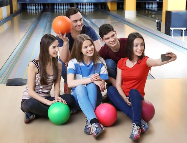 Amici che prendono selfie nel bowling club Foto Premium