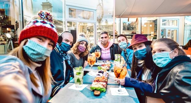 Amici che prendono selfie fuori al cocktail bar - fuoco selettivo sulla parte centrale del telaio Foto Premium