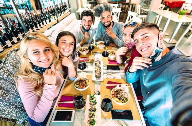 Amici che prendono selfie con maschere facciali al ristorante sushi bar Foto Premium