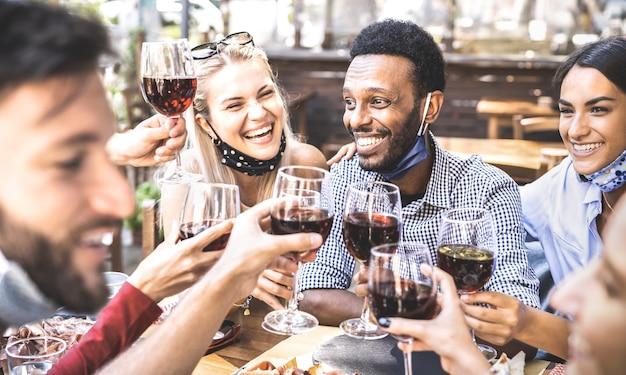 Amici che tostano il vino rosso al bar del ristorante che indossa la maschera facciale aperta Foto Premium