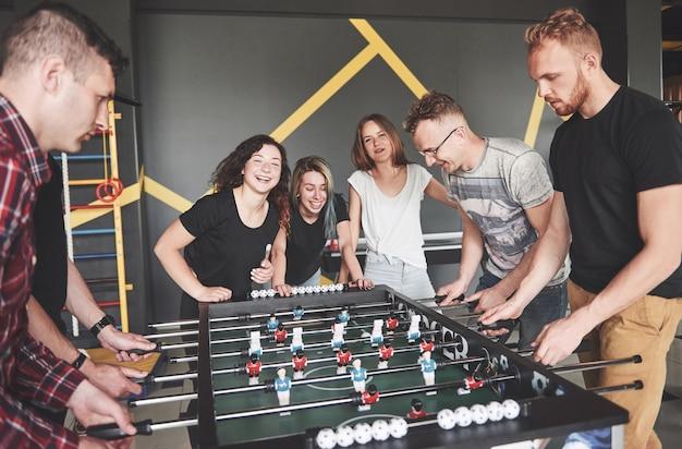 Gli amici insieme giocano a giochi da tavolo, calcio balilla, si divertono nel tempo libero. Foto Premium