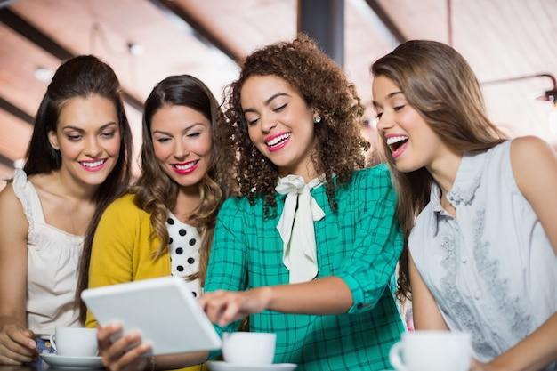 Amici che utilizzano tavoletta digitale nella caffetteria Foto Premium