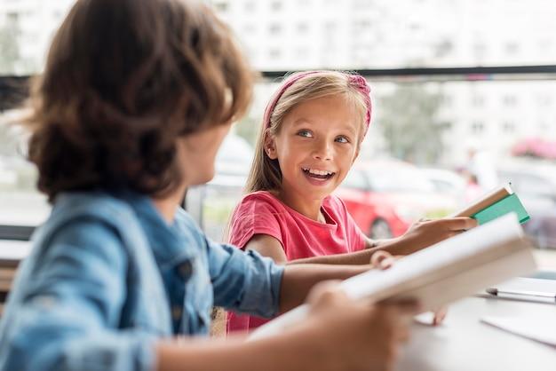 Amici che lavorano insieme per i compiti in biblioteca Foto Premium