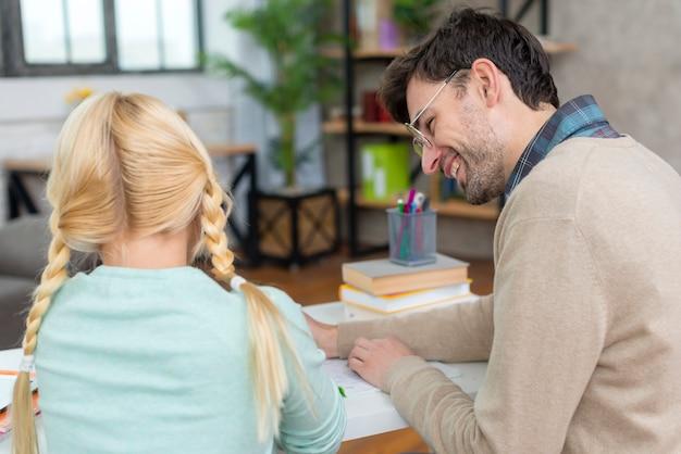 Dalla vista posteriore tutor e girl writing Foto Premium