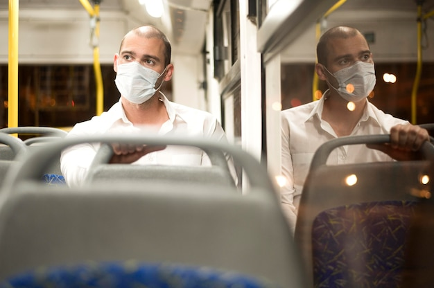 Bus di guida del maschio adulto di vista frontale con la mascherina medica Foto Premium