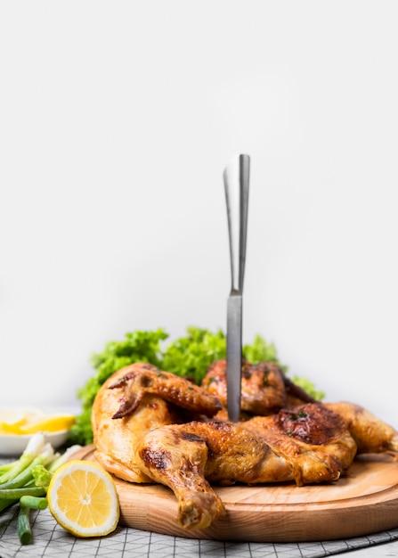Pollo intero cotto vista frontale sul tagliere con coltello e limone Foto Premium