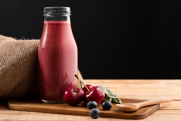Vista frontale mirtilli e ciliegie con frullato in bottiglia di vetro Foto Premium