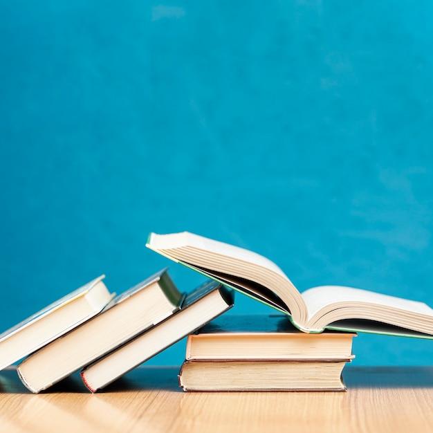 Libri di vista frontale sulla tavola con fondo blu Foto Premium