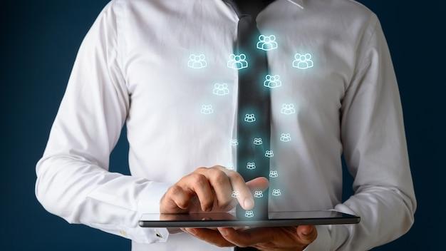 Vista frontale di un uomo d'affari utilizzando la tavoletta digitale con molte icone di persone incandescente che ne esce Foto Premium