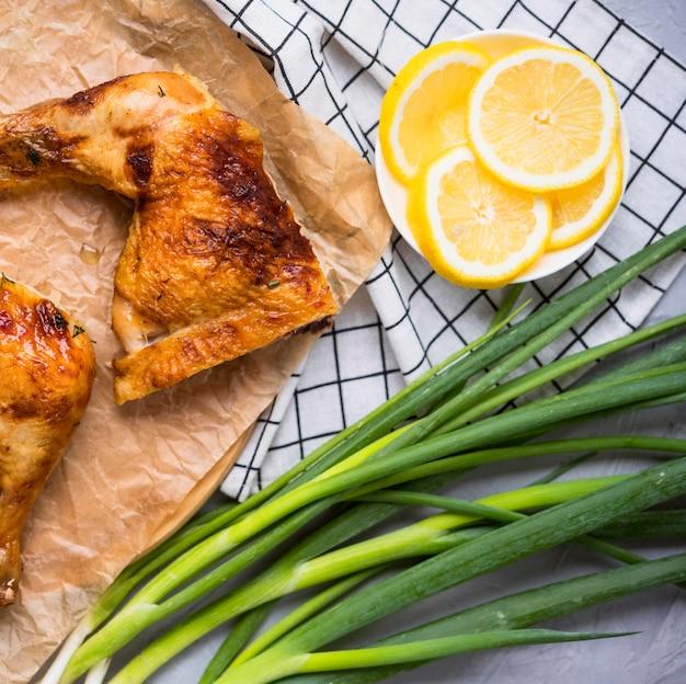 Cosce di pollo vista frontale con fette di limone Foto Premium
