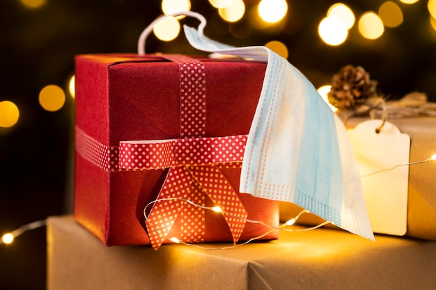 Vista frontale di regali di natale con maschera facciale Foto Premium