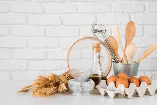 Uova di vista frontale con utensili da cucina Foto Premium
