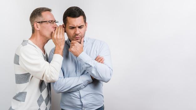Vista frontale del padre che bisbiglia al figlio Foto Premium