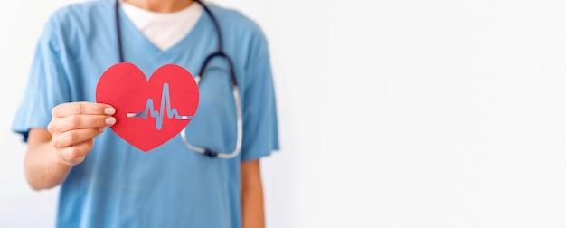 Vista frontale del medico femminile che tiene cuore di carta con lo spazio della copia Foto Premium