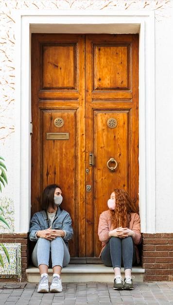 Vista frontale di amiche con maschere facciali seduto accanto alla porta Foto Premium
