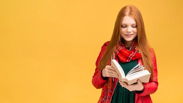 Libro di lettura della ragazza di vista frontale Foto Premium