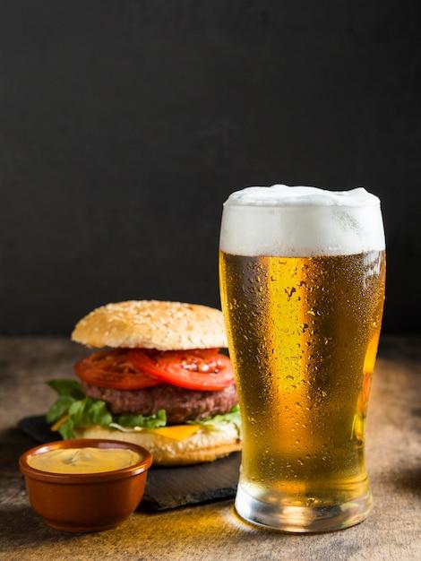 Vista frontale del bicchiere di birra con cheeseburger Foto Premium