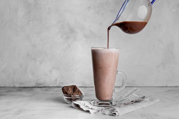 Vista frontale del bicchiere di latte al cioccolato con un panno Foto Premium