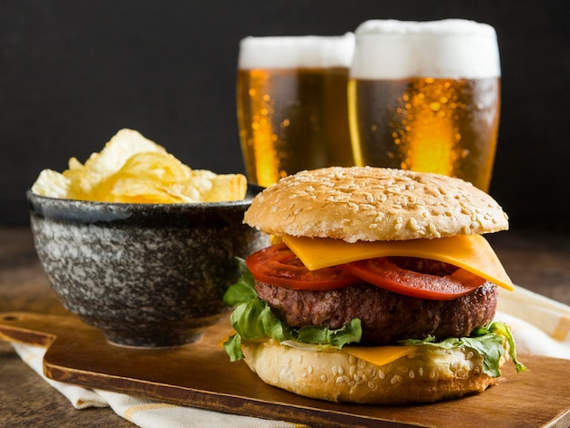 Vista frontale di bicchieri di birra con cheeseburger e patatine Foto Premium
