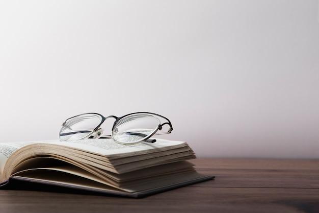 Vista frontale dei vetri sul libro aperto sulla tavola di legno Foto Premium