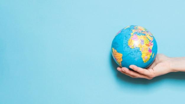Vista frontale del globo della tenuta della mano con lo spazio della copia Foto Premium