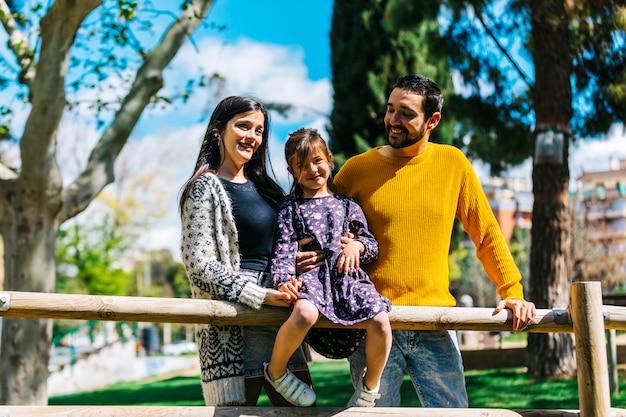 Vista frontale di una famiglia felice nel parco. padre madre e figlio insieme in natura Foto Premium