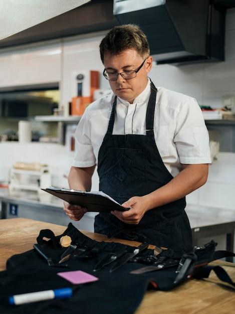 Vista frontale del cuoco unico maschio che controlla appunti in cucina Foto Premium