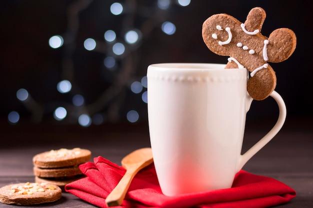 Vista frontale della tazza con omino di pan di zenzero e biscotti Foto Premium