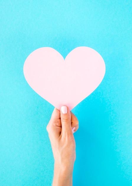 Vista frontale del cuore di carta tenuto a mano Foto Premium