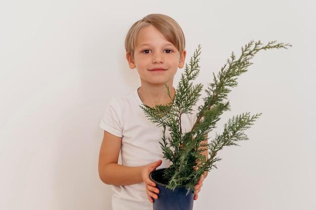 Vista frontale del ragazzo di smiley che tiene il vaso della pianta Foto Premium
