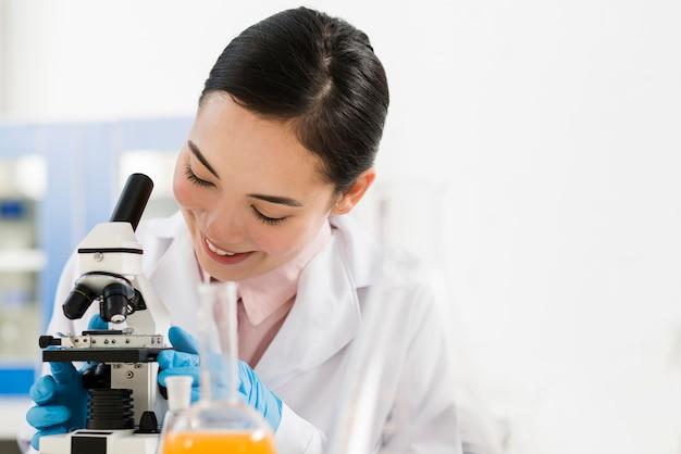 Vista frontale della scienziata e del microscopio femminili di smiley Foto Premium
