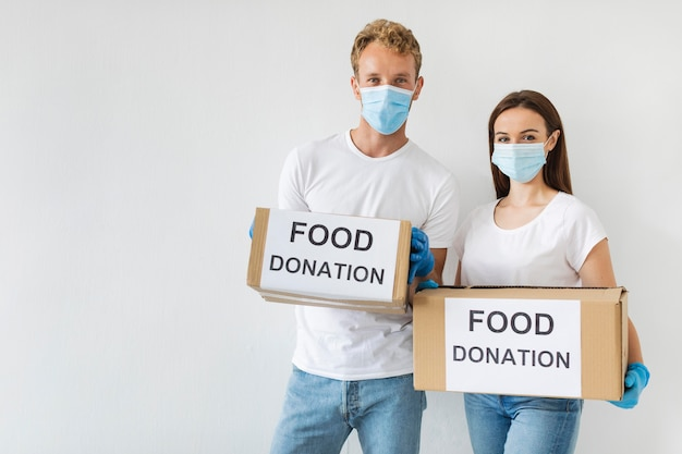 Vista frontale dei volontari che tengono le caselle di donazione con lo spazio della copia Foto Premium