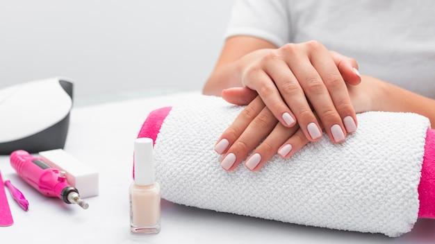 Donna di vista frontale che ottiene la sua manicure fatta al salone Foto Premium