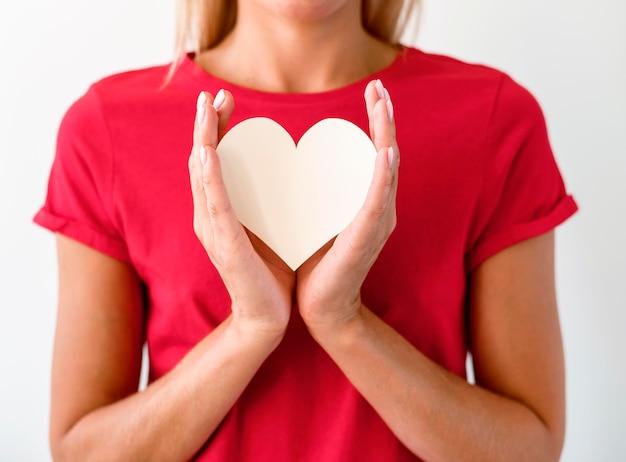 Vista frontale della donna in maglietta che tiene il cuore di carta Foto Premium