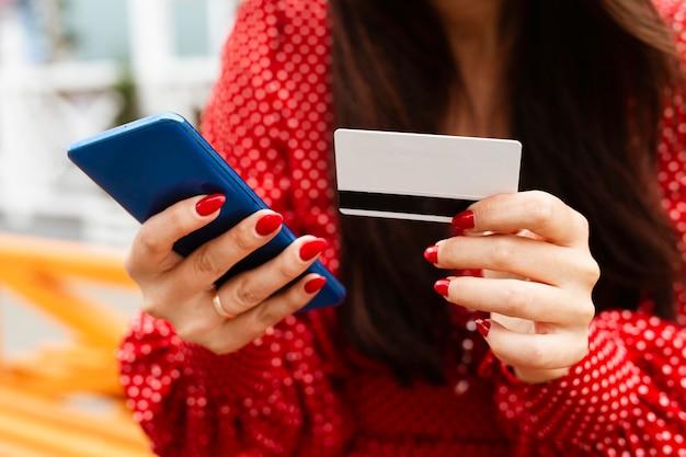 Vista frontale della donna che utilizza smartphone e carta di credito per fare acquisti online per le vendite Foto Premium
