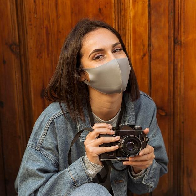 Vista frontale della donna con la maschera per il viso tenendo la fotocamera Foto Premium