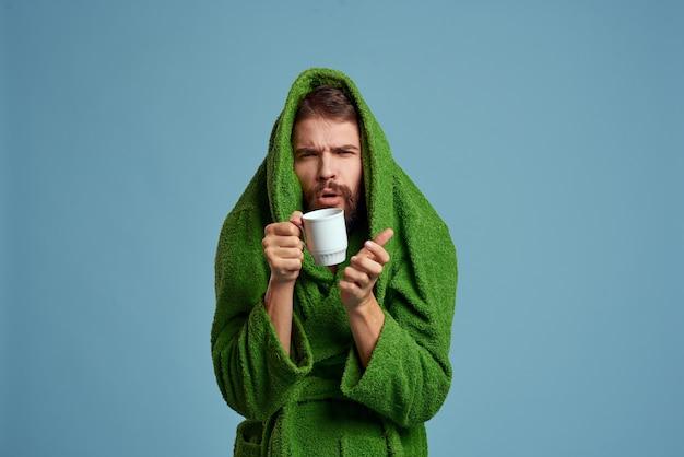 Uomo congelato in una calda veste con una tazza di bevanda calda su un blu Foto Premium
