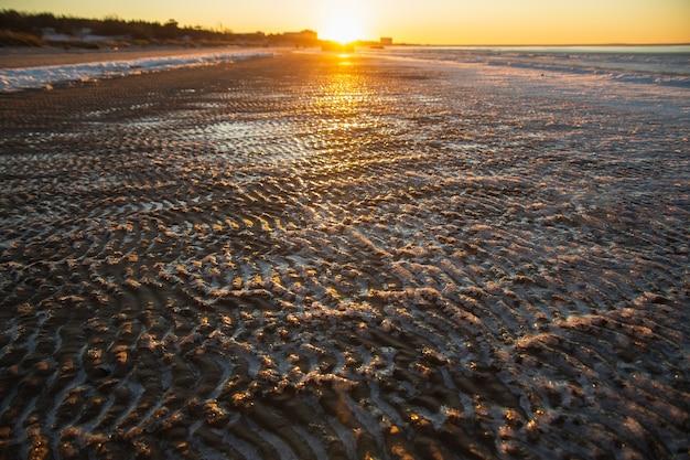 Spiaggia del mare ghiacciato sul sinset. onde di sabbia ricoperte di ghiaccio. Foto Premium